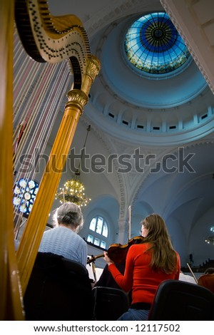 Playing violin at the symphony concert - stock photo