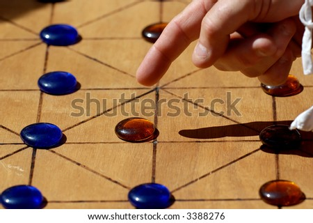 Playing with an old parlour game : Alquerque - stock photo