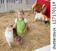 Playing with animals in petting zoo on a pumpkin patch. - stock photo