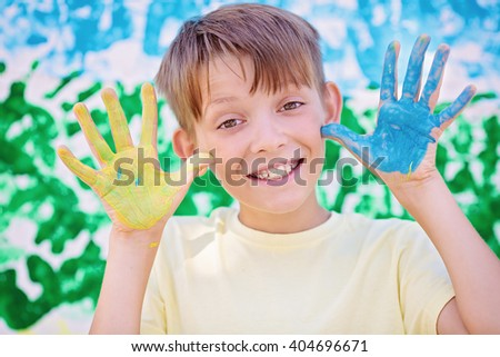 Playing with colors. Beautiful boy with colorful hands, creative child concept - stock photo