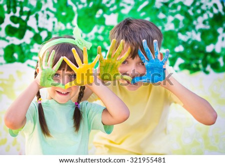 Playing with colors.  Beautiful children with colorful hands, creative child concept - stock photo