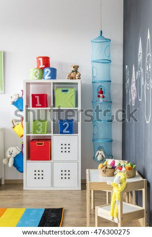 Playing zone in a child room with soft toys adn wooden table with chair for a kid