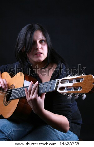 Plays on the classic guitar on black - stock photo