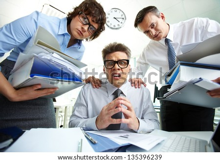Pleading accountant looking at camera being surrounded by his partners with huge piles of documents - stock photo