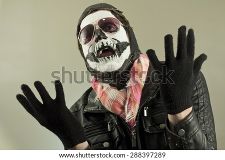 Pleading aviator with face painted as human skull - stock photo
