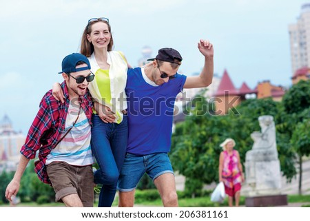 Pleasant and cheerful three friends hugging on the street and walk away. Young friends have fun together on the street and smile at each other. - stock photo