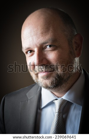 Pleasant business man with beard and bald head against a dark background