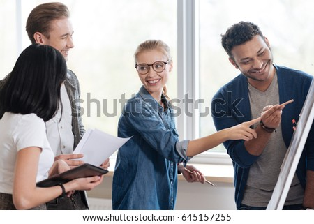 Pleasant cheerful woman standing with her colleagues