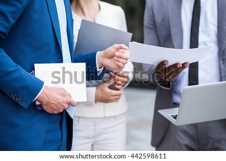 Pleasant colleagues holding papers