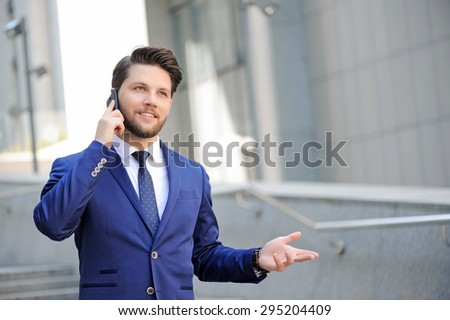 Pleasant conversation. Nice bearded businessman keeping his hand raised and talking on mobile phone while expressing positivity.