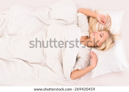 pleasant dreams for young attractive blonde woman on white bed - stock photo