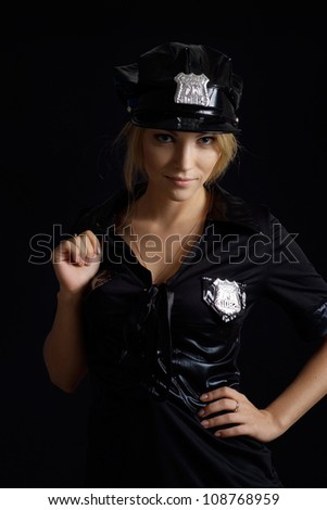 Pleasant girl in a uniform of  police officer on a black background - stock photo