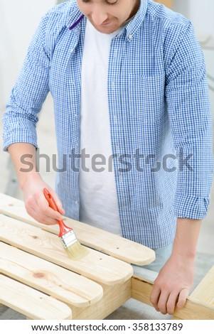 Pleasant man painting sled - stock photo