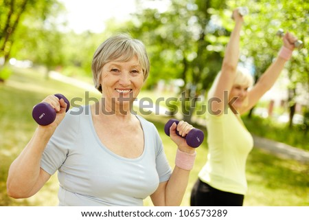 Pleasant mature females working out in the open air - stock photo
