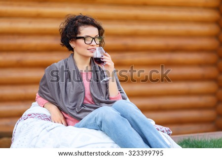 Pleasant moment. Nice charming young attractive girl sitting in the armchair near wooden wall while drinking wine - stock photo