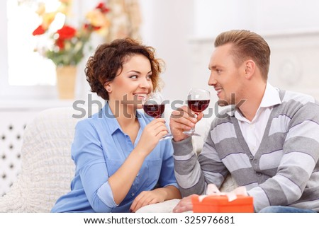 Pleasant moment. Upbeat happy young couple drinking wine and sitting at the table while looking at each other - stock photo