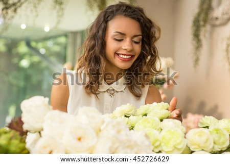 Pleasant shopping. Portrait of a stunning young African woman choosing flowers at the flower shop