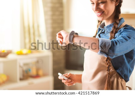 Pleasant smiling woman standing in the kitchen.  - stock photo