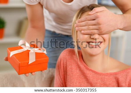 Pleasant surprise. Boyfriend covers his girlfriends eyes before giving her a present.  - stock photo