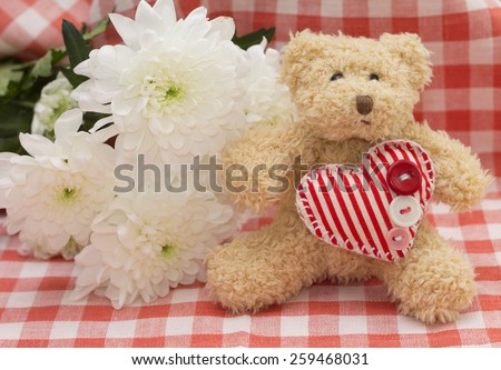 Pleasant surprise to woman on March, 8 - cute teddy bear and flowers - stock photo