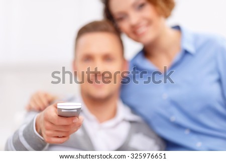 Pleasant time. Selective focus of remote control in hands of pleasant handsome young man holding it while watching TV with his girlfriend - stock photo