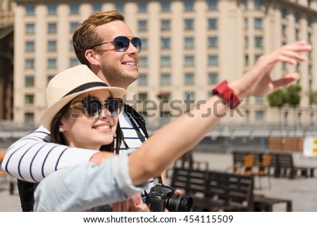Pleasant time spending. Cheerful loving couple bonding to each other and having a walk while looking up