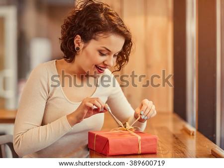 Pleasant woman opening present - stock photo