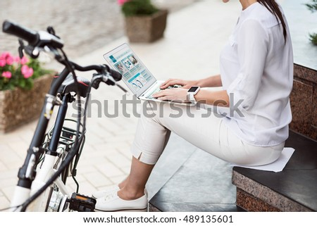 Pleasant young woman sitting outside in the street