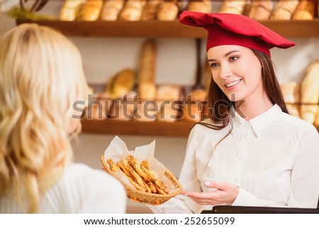 Please enjoy. Beautiful young female baker in a lovely hat giving a basket of pretzels to a customer and smiling while standing against rows of fresh baked bread  - stock photo