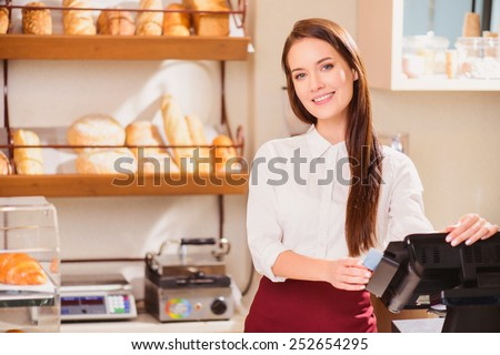 Please enjoy. Closeup image of beautiful young female baker stretching out two paper cups while standing against cafe with selective focus - stock photo