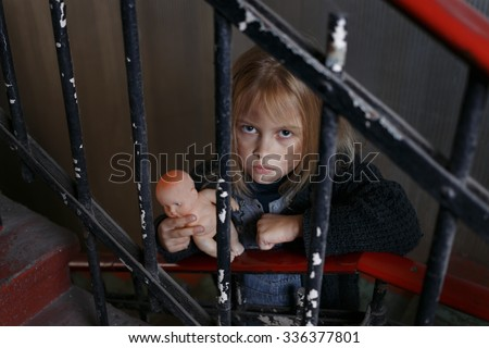 Please help me. Poor little girl standing on staircases and holding toy while feeling miserable - stock photo