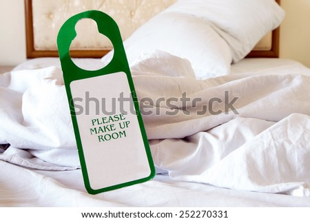 Please Make Up Room sign on an untidy bed (Focused on the sign) - stock photo