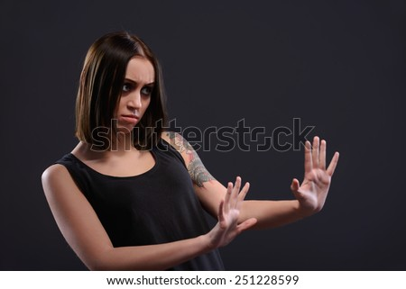 Please no. Terrified young woman looking at somebody and stretching out hand while standing against black background - stock photo