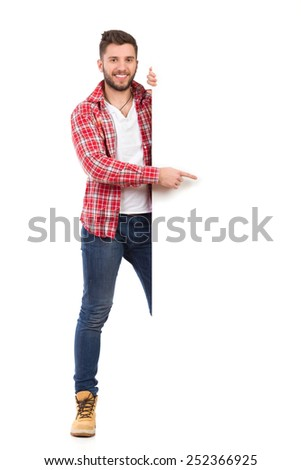 Please read this. Handsome young man in jeans and lumberjack shirt standing behind white banner and pointing. Full length studio shot isolated on white.