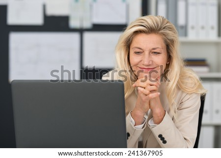 Pleased attractive middle-aged businesswoman sitting at her desk with a broad smile reading information on her laptop screen