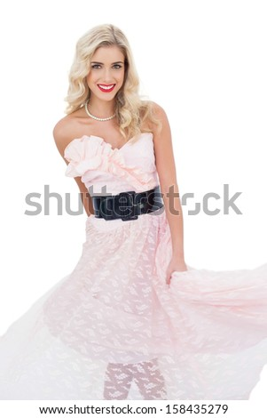 Pleased blonde model in pink dress posing shaking her dress on white background