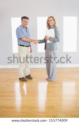 Pleased blonde realtor and mature buyer shaking hands in an empty room - stock photo