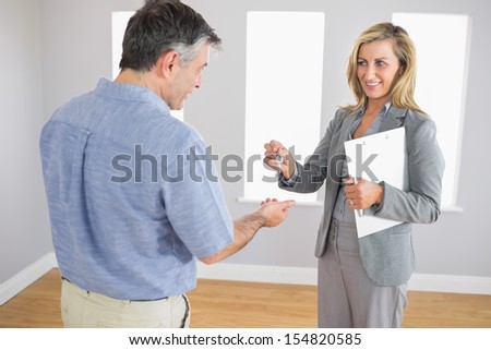 Pleased blonde realtor holding a briefcase and giving a key to a mature buyer in an empty room - stock photo