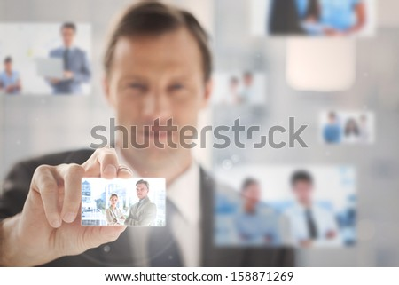 Pleased businessman picking a business team picture among blurred others - stock photo