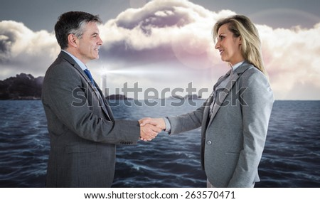 Pleased businessman shaking the hand of content businesswoman against calm sea with lighthouse - stock photo