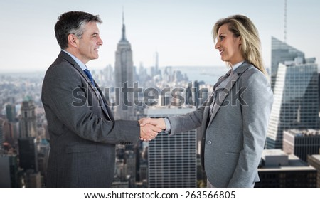 Pleased businessman shaking the hand of content businesswoman against new york