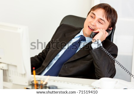 Pleased businessman sitting at office desk and talking on phone - stock photo