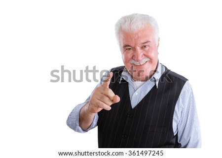 Pleased handsome male pensioner in vest with mustache on isolated background conversing and pointing finger - stock photo