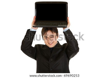Pleased modern businessman holding laptop with blank screen over his head isolated on white