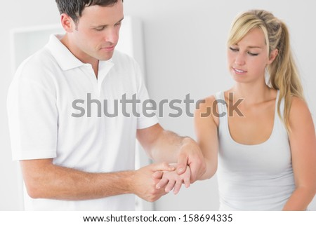 Pleased physiotherapist examining patients hand in bright office