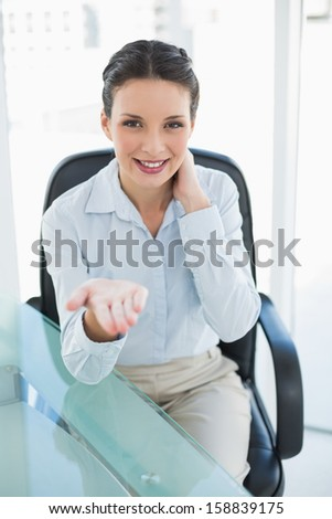 Pleased stylish brunette businesswoman presenting her hand in bright office