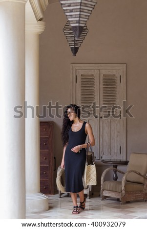 Pleased woman in black dress after shopping with straw bag in luxury mall with white walls and columns