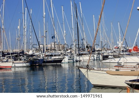 Pleasure boats and yachts moored in the sheltered water of a marina under a sunny blue summer sky