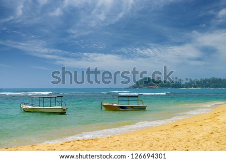 Pleasure boats on the beach of the ocean. Beautiful shores of the Indian ocean