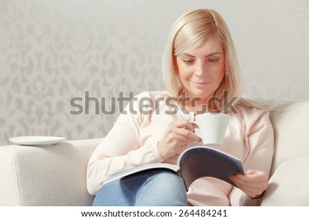 Pleasure of being at home. Blond middle aged woman holds a magazine copyspace and cup of coffee while sitting at the sofa at home - stock photo